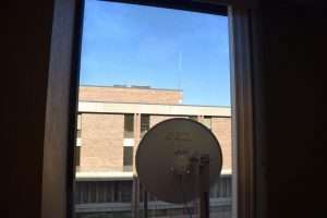 View of microwave dish pointing out the window to a dish on the roof of an adjoining building